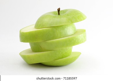 A green apple sliced diagonally. Isolated on neutral background.