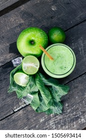 Green apple smoothie in glass and kale leaves on wooden table