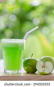 green apple smoothies on wooden table