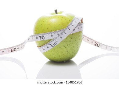 Green apple and tape measure on white background