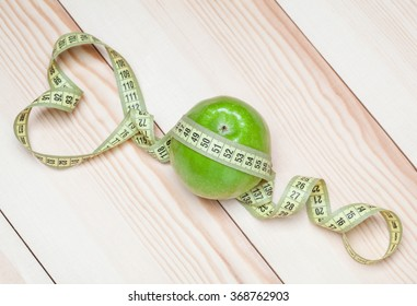 Green apple with tape measure on wooden background