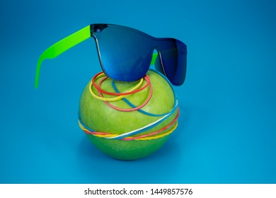 Green apple tied in colorful rubber bands and fashion sunglasses over a blue background. Simplicity back to school or diet, aerobic concept with copy space