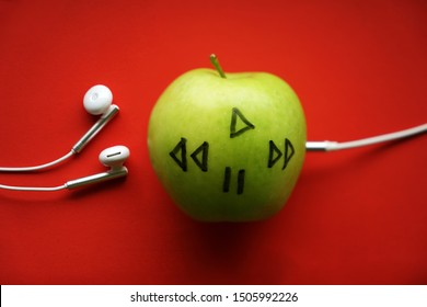 green apple in which headphones are connected. red background. White music head phones on a red table, plugged into an Apple fruit in background