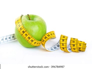 A green apple wrapped in measuring tape isolated on white backgroun