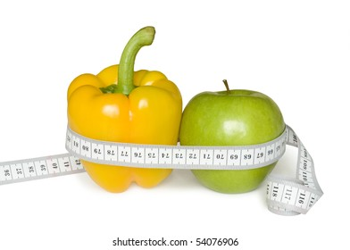 green apple and yellow paprika with tape measure