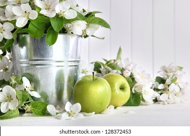 Green apples with blossoms on wooden table