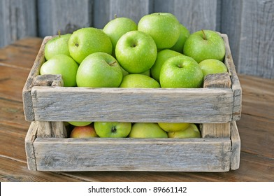 Green apples in a box on a wooden table.
