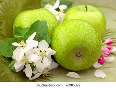 Green apples with flowers close up