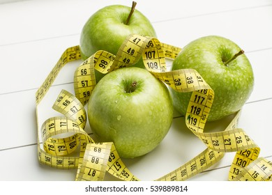 Green apples and a measuring tape