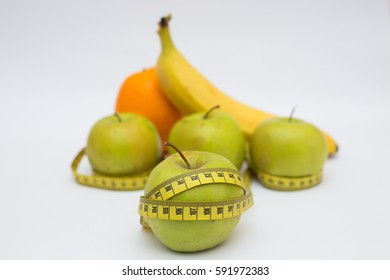 green apples and measuring tape banans orange on a white background. Healthy lifestyles concept