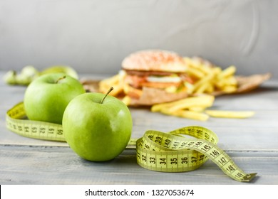 green apples on the background of a burger and fries. Sewing Tape Measures on the food. concept of opposition  healthy food and junk food. selective focus