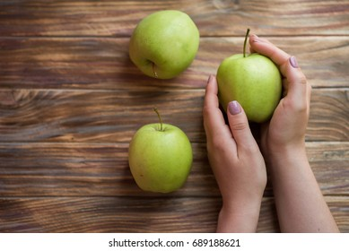 Green apples on a brown wooden background