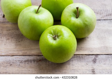 green apples on wooden background, top view