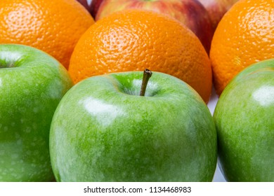 Green apples, oranges and red apples on white table