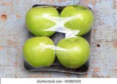 Green apples packed under plastic film