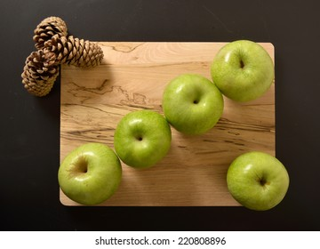green apples and pine cones on wooden chopping board isolated on black abstract background