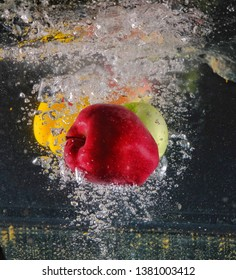 Green apples, red apples and yellow sweet peper fall into the water,  many air bubbles occurring with splashes on a black background.