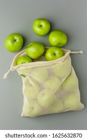 Green apples in a reusable grocery white cotton bag on a gray background. Top view, close-up.