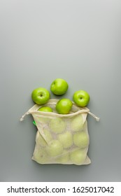 Green apples in a reusable white cotton bag on a gray background. Top view, image with copy space.