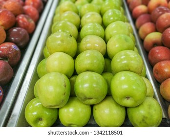 green apples for sale in supermarket in hortifruti section with blurred background