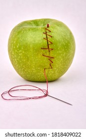 Green apple's sewed with red stitches. Practice of stitching. Healing green apple.