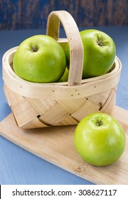 Green apples in a wooden basket on a blue wooden background.