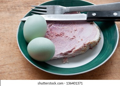 Green araucana eggs sit on a plate with a thick slice of ham. These eggs are from Araucana chickens and appear in their natural colors--they are not dyed.