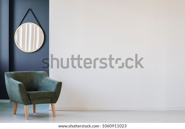 Green armchair against blue wall with round mirror in living room interior with copy space on white wall