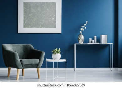 Green armchair against the wall with silver painting in navy blue living room interior with flowers