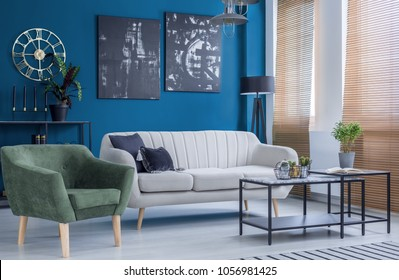 Green armchair and couch in colorful living room interior with black posters on blue wall