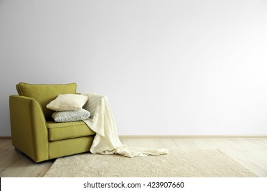 Green armchair on light wall background