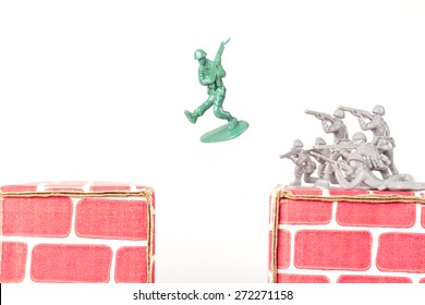 Green army man jumps ravine to escape gray army