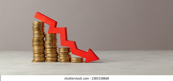 Green arrow down over stack of coins by ladder on gray background. Copy space for text