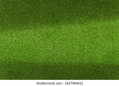 Green artificial golf grass texture. Bright image with some shadows