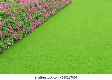Green artificial grass with pink flower
