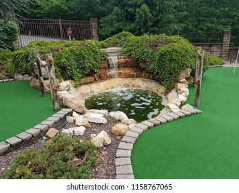 green artificial grass and rocks on miniature golf course
