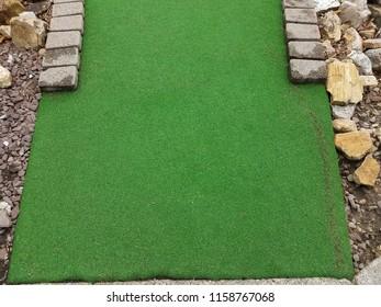 green artificial grass and rocks on miniature golf course