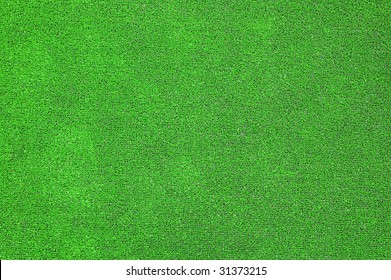 A green artificial grass for sports fields, covering, gardens. Plastic or grass background texture