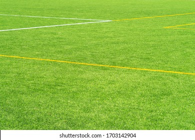 Green artificial grass turf soccer football field background with white and yellow line boundary. Top view