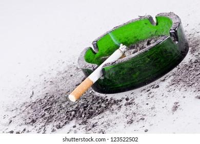 Green ashtray with smoked cigarette/Green ashtray and cigarette