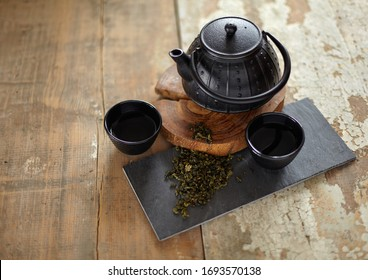 Green asian tea on vintage wooden table. Top side view of teapot and cups on black rock with copy space