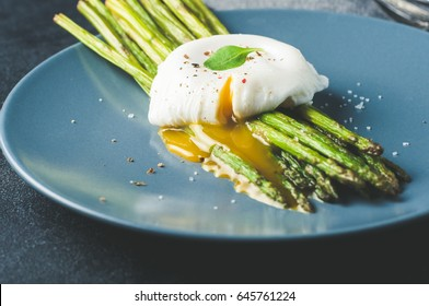 Green asparagus and boiled poached egg on a blue plate over a dark concrete background