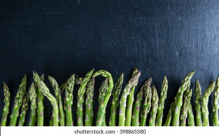 Green Asparagus (close-up shot) on a slate slab (selective focus)