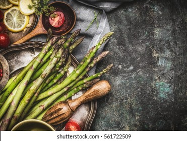 Green asparagus cooking preparation with cooking spoon and ingredients on rustic background, top view, place for text