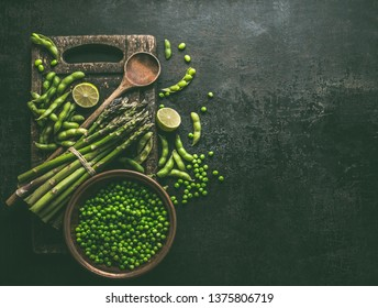 Green asparagus with edamame soybeans, lime and green peas on dark rustic kitchen table background, top view. Copy space. Healthy vegetarian food . Green cooking ingredients.