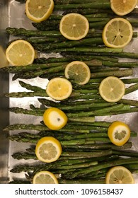 Green asparagus with lemon slices on a baking tray