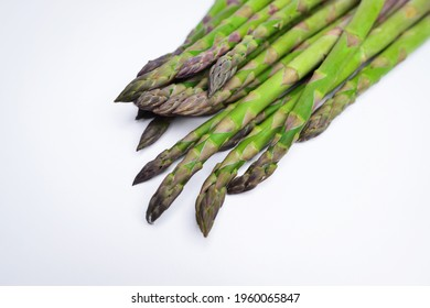 Green asparagus sticks isolated on white background. Studio shot. Vegetables: Asparagus Isolated on White Background. Fresh ripe asparagus on a white background.