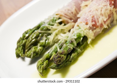 green asparagus wrapped in ham, covered with grated parmesan cheese, close-up