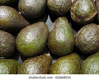 Green Avacados stacked at farmers' market