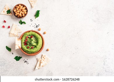 Green Avocado Hummus bowl, healthy vegan dip. Organic green herbal, spinach hummus,  spread  with pita bread and vegetables. Top view, copy space.